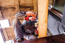 Man grinding planks of wood for home construction.