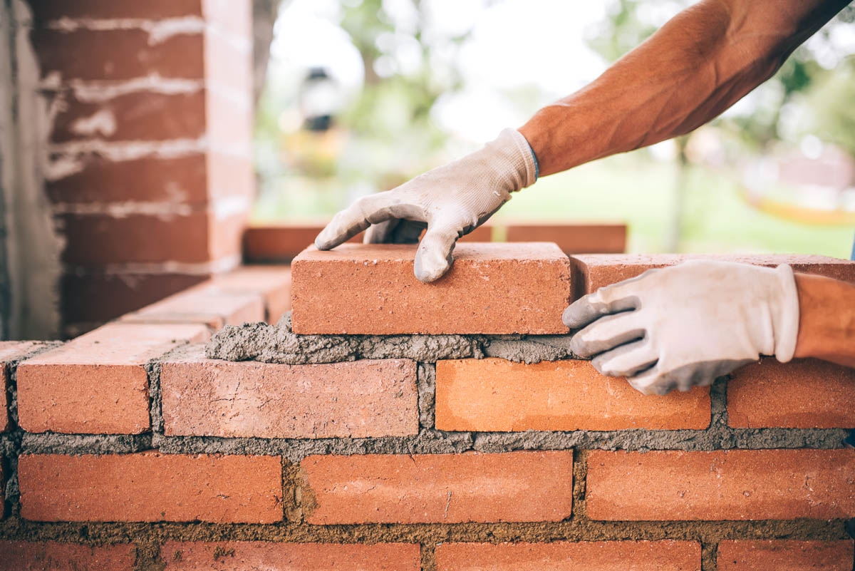 professional construction worker laying bricks and building barb